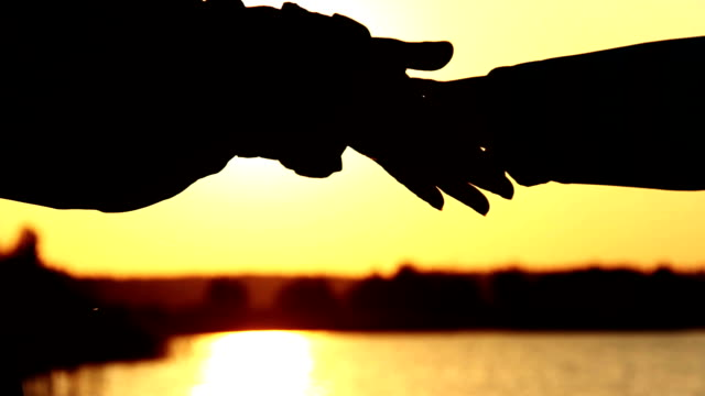 Holding Hand At River Sunset, mother takes child's hand at sunset video