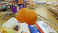 Holiday shopping for Halloween. Trolley with shopping bags and a large pumpkin goes to the supermarket video
