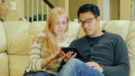 Home and Technology. A young couple enjoys the tablet. Asian man and Caucasian woman video