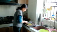 Home cooking: a senior woman cutting vegetables video