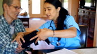Home healthcare nurse assists senior patient with arm brace video