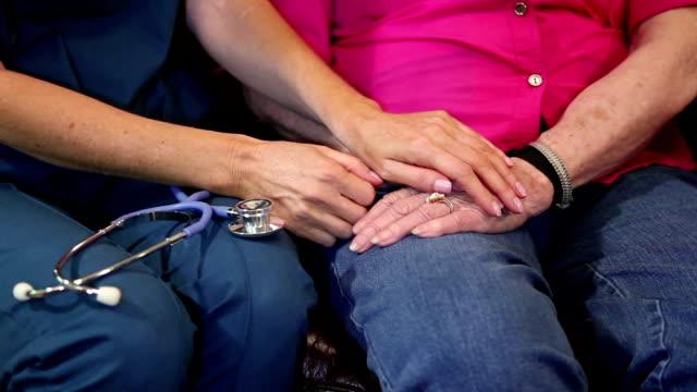 Home healthcare nurse comforts senior woman. Hands. video
