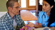 Home healthcare nurse or physical therapist reviews senior patient's care plan video
