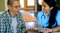 Home healthcare nurse reviews information with senior patient video