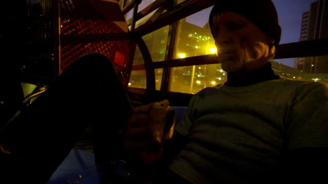 Homeless man sitting on street at night eating sandwich video