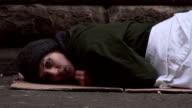 Homeless woman lying on street looking in distress video