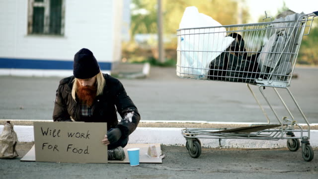 Homeless young man counting how much money he got holding paper cup in the hands and sitting near shopping cart at the street video
