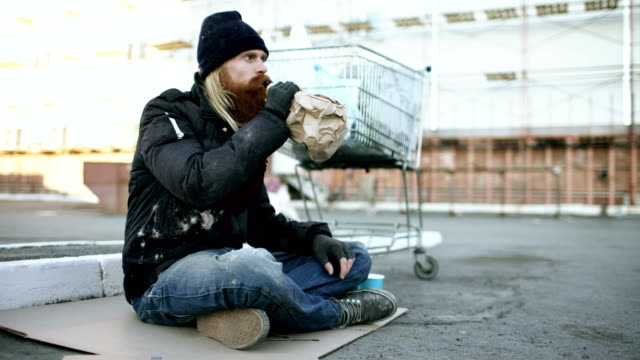 Homeless young man in dirty clothes drink alcohol sitting near shopping cart on the street at cold winter day video