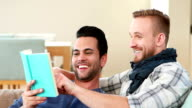Homosexual couple men reading a book together video