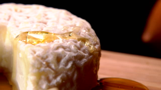 Honey drains from a piece of French cheese video