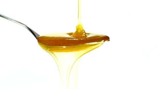 honey dripping on a spoon close-up video