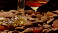 Honey pouring on nuts left to right . With brandy. Slow motion video