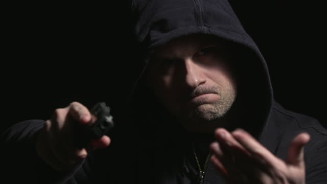 Hooded Man Walks Up and Points Gun Motions Hand Rack Focus video