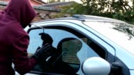 Hooded thief opens the car door window using a screwdriver and suddenly steals a notebook video