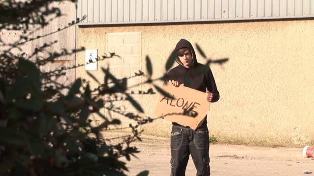 Hoody holding board saying 'ALONE' - HD & PAL video