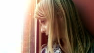 hopeless young woman lost in her thoughts: sad woman looks out her window video