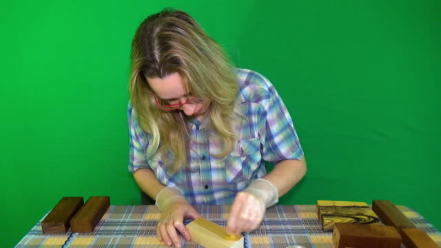 Hornbeam wood. The bar of solid wood is covered with stain. The girl covers a bar of rare wood with lacquer. The joinery impregnates the wood with wax. Chroma Key video
