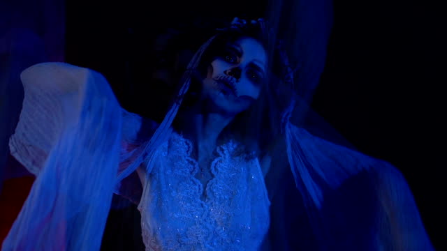 Horror scene from the film with dead girl in white wedding dress and veil. Creepy visual hallucination in the form of changing images of young girl with skull mask on her face video