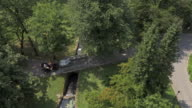 AERIAL Horse carriage going across a bridge in the park video