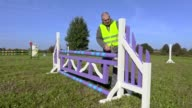 Horse handler with measure tape near hurdle video