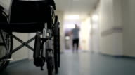 Hospital corridor with empty wheelchair and man walking away video