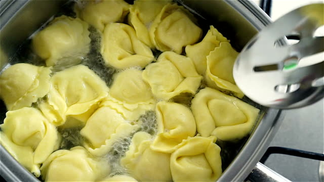 Hot boiling tortellini in a pan and checking if ready video
