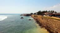 Hot summer day at resort town, ocean waves splashing against rocky shore video