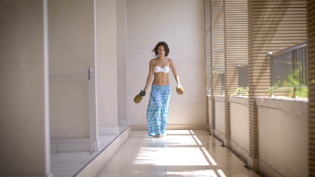 Hotel Corridor. The girl in a bathing suit and blue trousers free, in the hands of her two pineapple. Brunette played pineapple and shows a Spanish dance video