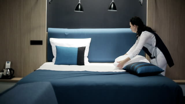 Hotel: Maid making bed in hotel room video