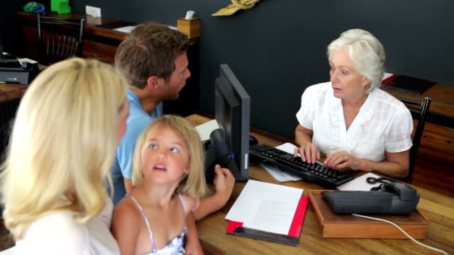 Hotel Receptionist Helping Family To Check In video
