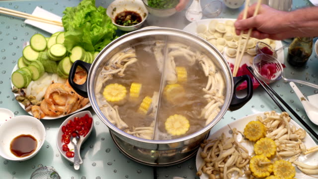 Hotpot concept of Asian cuisine. Boiling broth on the table. Cooking meat in broth in skimmer spoon video