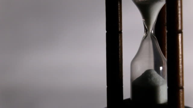 Hourglass flowing and suddenly stop, time and life conceptual video, close up shot,low key lighting video