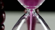 Hourglass in wooden stand. Pink sand. Close up video