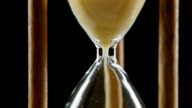 Hourglass is ticking. Yellow sand. Black. Close up video
