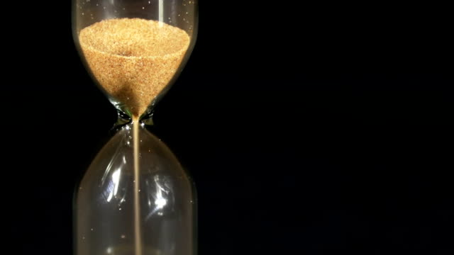 Hourglass on a Black Background, the sand Falls Inside video