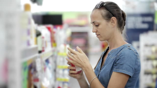 Housewife choosing body care products in supermarket. video