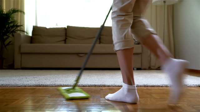 Housewife dancing with a mop in the living room. Legs close-up. Slow motion video