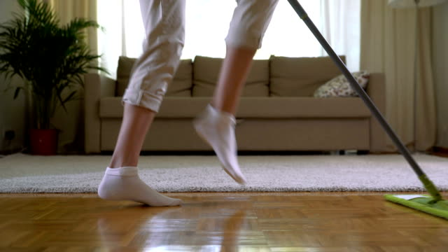Housewife dancing with a mop in the living room. Legs close-up video