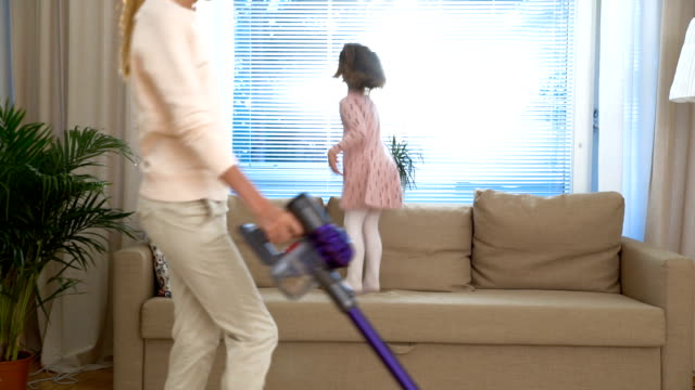 Housewife dancing with a vacuum cleaner in living room. Her little daughter jumping on the couch. Slow motion video