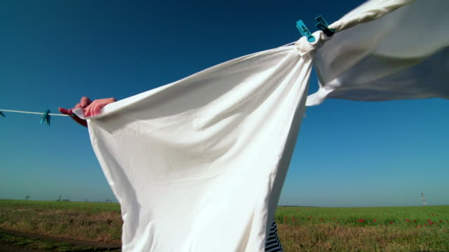 Housewife hanging white laundry on washing line video