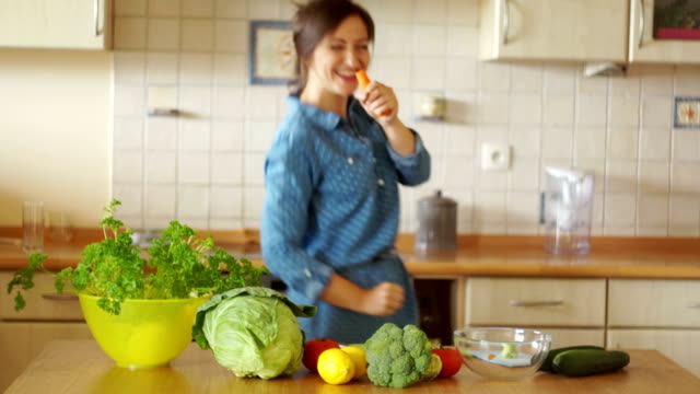 A housewife in the kitchen is in a good mood. She cuts vegetables and sings with a carrot as if she were a microphone. video