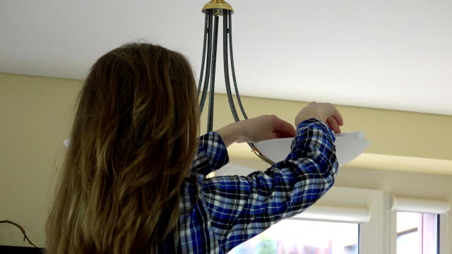 housewife woman changing light bulbs. Back view. video