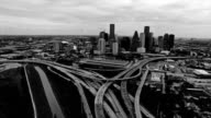 Houston Texas Aerial Fly By Skyline Cityscape with Traffic on Interstate I10 over interchanges and loops Black and white video