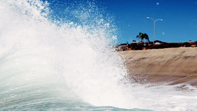 Huge backwash and wave crashing on the golden summer sand of California with Palm Trees in the background. Shot in slowmo on the Red Dragon at 300FPS. video