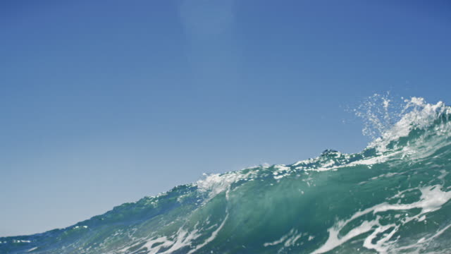 Huge beautiful wave POV as wave breaks over camera on shallow sand beach in the California summer sun. Shot in slowmo. video