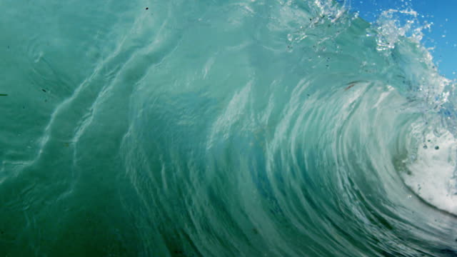 Huge beautiful wave POV as wave breaks over camera on shallow sand beach in the California summer sun. Shot in slowmo on the Red Dragon at 300FPS. video