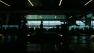A huge cold in the airport terminal. Silhouettes of people who are in a hurry on a plane on the moving walkway, as well as the seat where your flight expected video