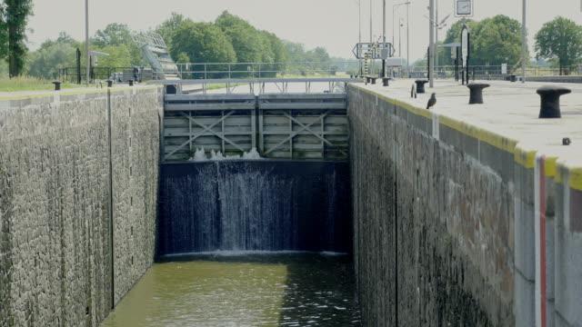 Huge door at overflow cargo lock chambers. Water dam on river with pass. video