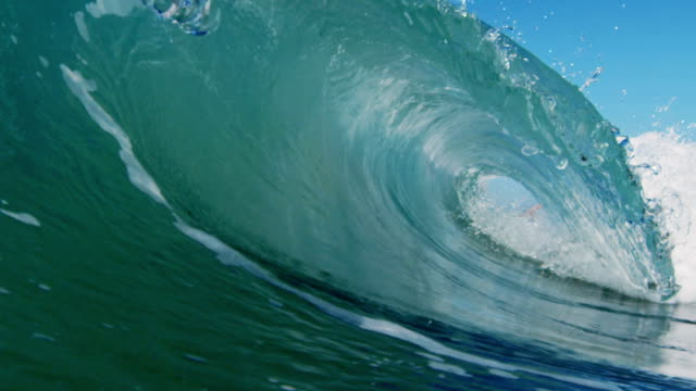 Huge perfect barreling beautiful wave POV as wave breaks over camera on shallow sand beach in the California summer sun. Shot in slowmo on the Red Dragon at 300FPS. video
