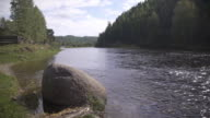Huge stone perched near riverbank, dark forest is across the river video